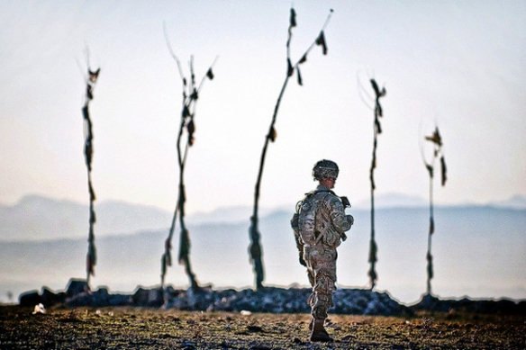 Spc. Jon Saladin, a paratrooper with the 82nd Airborne Division's 1st Brigade Combat Team, walks past an Afghan graveyard during a US–Afghan patrol on April 30, 2012, Ghazni province, Afghanistan. Saladin serves with Company A, 2nd Battalion, 504th Parachute Infantry Regiment. US Army photo by Sgt. Michael J. MacLeod.