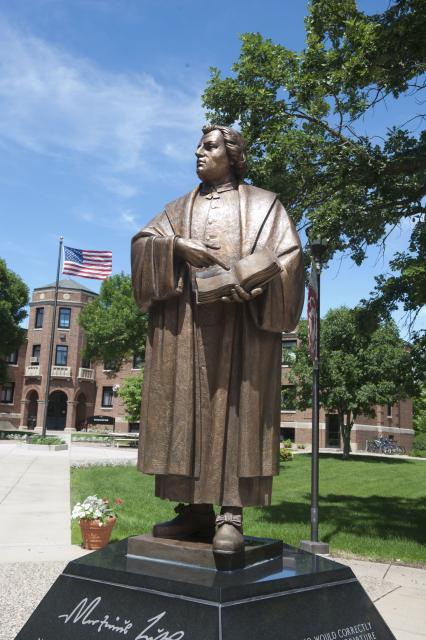 "Martin Luther College (statue of Luther pointing to a passage in the Bible and asking ""Who wrote this shit?"""