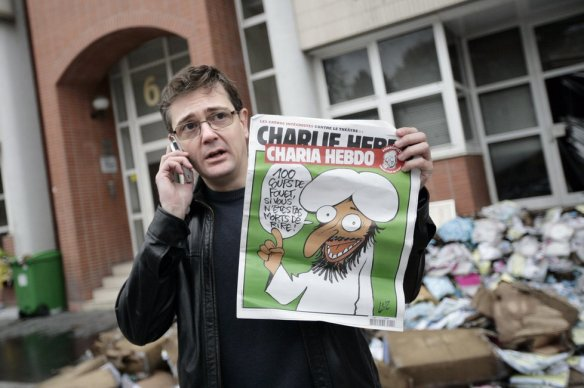 Stéphane Charbonnier, one of today's dead, outside the firebombed office of Charlie Hebdo in 2011.